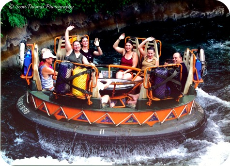 Soaked riders wave to the photographer towards the end of the Kali River Rapids in Disney's Animal Kingdom, Walt Disney World, Orlando, Florida