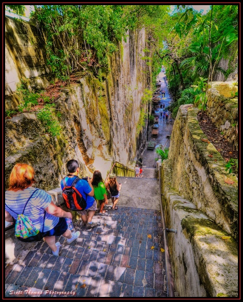 People walking down the 65 steps of the Queen's Staircase in Nassau, Bahamas.