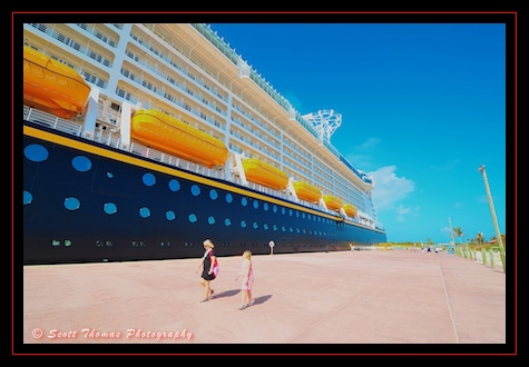 Guests walking past the docked Disney Dream at Castaway Cay.