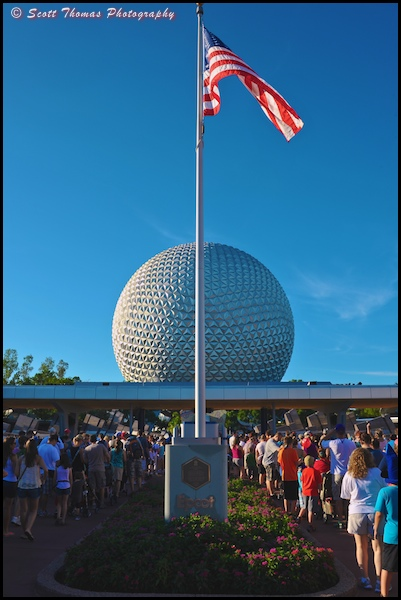 People lined up on either side of the dedication plaque flagpole outside Epcot on October 1, 2012, Walt Disney World, Orlando, Florida.