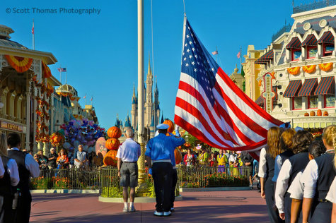 Veteran of the Day and Disney Security pay homage as the flag is lowered during the Flag Retreat ceremony in the Magic Kingdom, Walt Disney World, Orlando, Florida.
