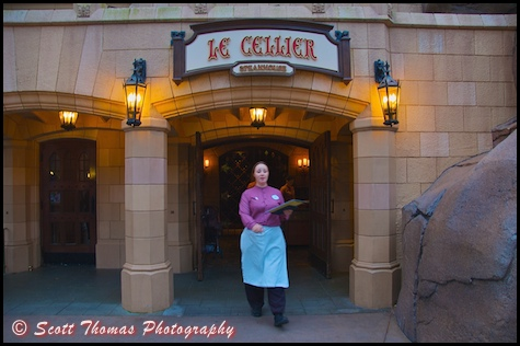 A Cast Member coming out to call out a party's name to eat at Le Cellier in the Canadian pavilion in Epcot's World Showcase, Walt Disney World, Orlando, Florida