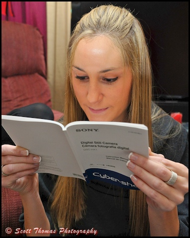 A young woman reads the manual to her new digital camera.