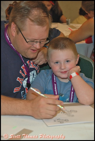 A father helps his son draw Mickey Mouse in the Kid's Room at MagicMeets in Harrisburg, Pennsylvania.