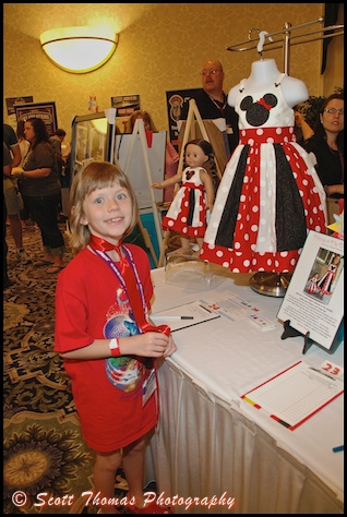 A young MagicMeets attendee admires the Minnie and Me dress set during the Dream Team Auction.