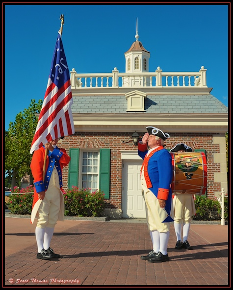Member of the Spirit of America Fife and Drum Corps saluting the American flag in front of the American Adventure in Epcot, Walt Disney World, Orlando, Florida.