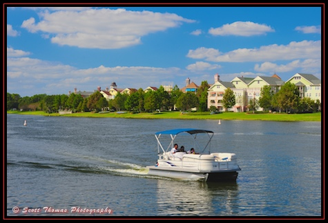 A guest pilots a pontoon rental boat past the Saratoga Springs Resort, Walt Disney World, Orlando, Florida.