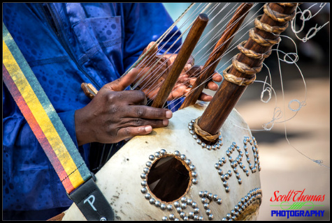 Close up of a muscian's hands playing a mandinka harp in the African village of Harambe at Disney's Animal Kingdom, Walt Disney World, Orlando, Florida