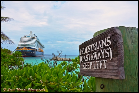 A sign on Castaway Cay with the Disney Dream cruise ship in the background.
