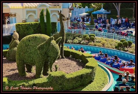 Elephant and giraffe topiaries watch over It's a Small World boats filled with guests pass by at Disneyland, Anaheim, California
