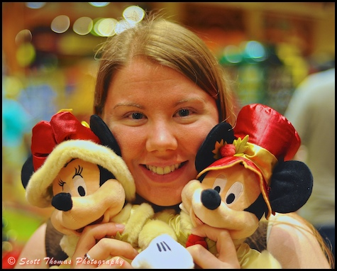 A young woman hugs Mickey and Minnie Mouse plush toys in the World of Disney store in Downtown Disney Marketplace, Walt Disney World, Orlando, Florida.