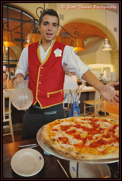 Via Napoli server in brightly colored costume serving up a pizza in Epcot, Walt Disney World, Orlando, Florida