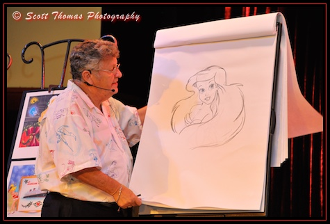 Don 'Ducky' Williams, famed Disney character artist, with a finished a portrait of Ariel during an event in Epcot's Odyssey restaurant, Walt Disney World, Orlando, Florida