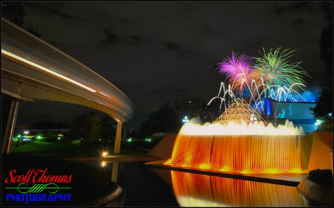 A monorail passes Journey into Imagination's Reverse Waterfall as Illuminations fireworks explode overhead in Epcot's Future World, Walt Disney World, Orlando, Florida