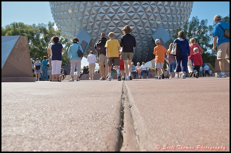 A low view of people walking towards Spaceship Earth in Epcot, Walt Disney World, Orlando, Florida