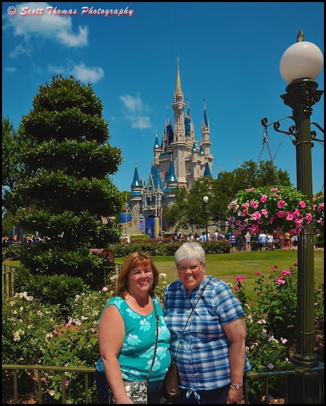 Guests pose in front of Cinderella Castle at the Magic Kingdom, Walt Disney World, Orlando, Florida