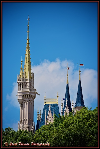 Spires and towers of Cinderella Castle poke above trees in the Magic Kingdom, Walt Disney World, Orlando, Florida