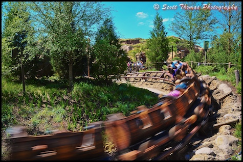 Seven Dwarfs Mine Train flying by in Fantasyland at the Magic Kingdom, Walt Disney World, Orlando, Florida