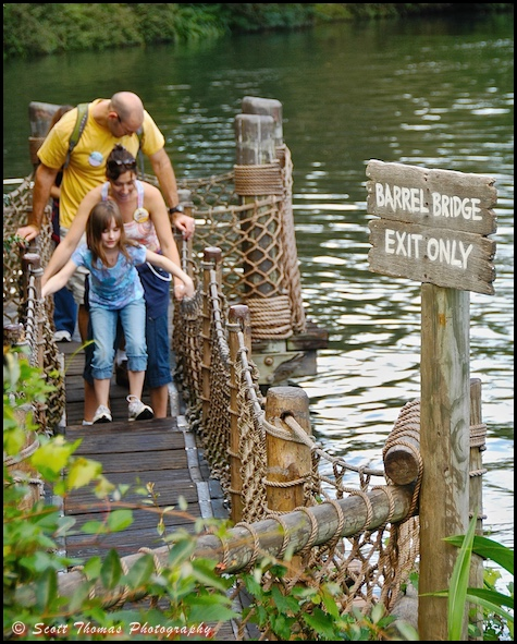 A family walks over the barrel bridge on Tom Sawyer Island in the Magic Kingdom, Walt Disney World, Orlando, Florida
