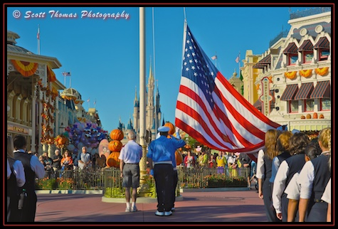 Veteran of the Day and Disney Security pay homage as the flag is lowered during the Flag Retreat ceremony in the Magic Kingdom, Walt Disney World, Orlando, Florida