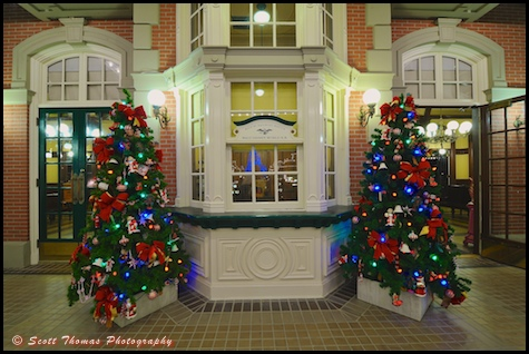 Main Street Railroad Station office framed by a pair of Christmas trees in the Magic Kingdom, Walt Disney World, Orlando, Florida