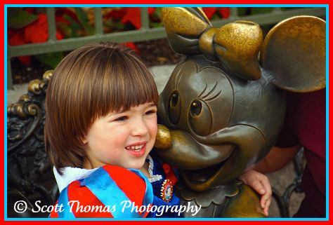 A girl sitting in Minnie Mouse's lap in the Magic Kingdom, Walt Disney World, Orlando, Florida.
