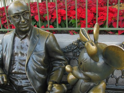 Minnie sitting with Roy O. Disney in their statue, Sharing the Magic
